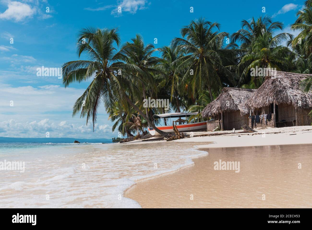 Picturesque view of huts, boat and tropical forest on sand beach near sea and blue sky in San Blas islands, Panama Stock Photo