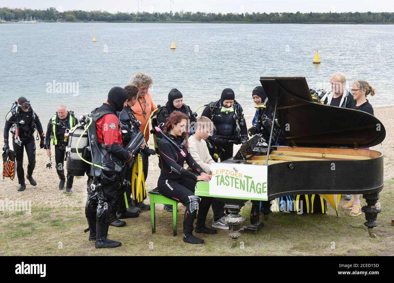31 August 2020, Saxony, Leipzig: On the beach of the Kulkwitzer See in front of the diving school Delphin, the 15-year-old pianist Florian shows his group of sport divers from Ulm/Neu-Ulm (Baden-Württemberg/Bavaria) and diver Selina Schwarz from Leipzig (front right) different keystrokes on an old grand piano from 1880 which is placed outside. During a festival lasting several days, the 4th Leipzig Keyboard Days (until 13.09.20), a total of ten pianos and grand pianos sponsored by institutions and companies will be on display at various locations in the large new building area. The musical ins Stock Photo