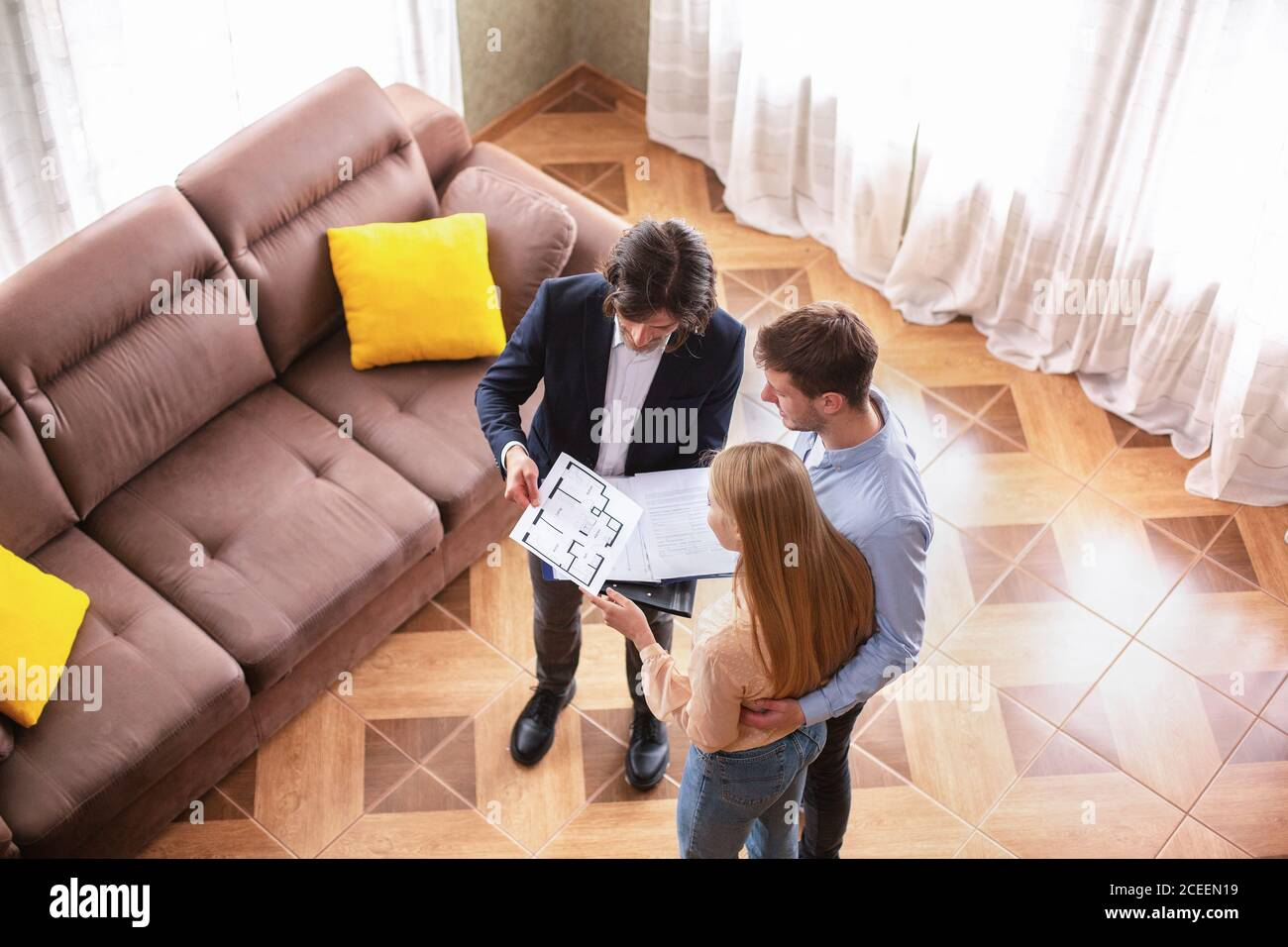 Above view of real estate agent showing house plan to young customers indoors Stock Photo
