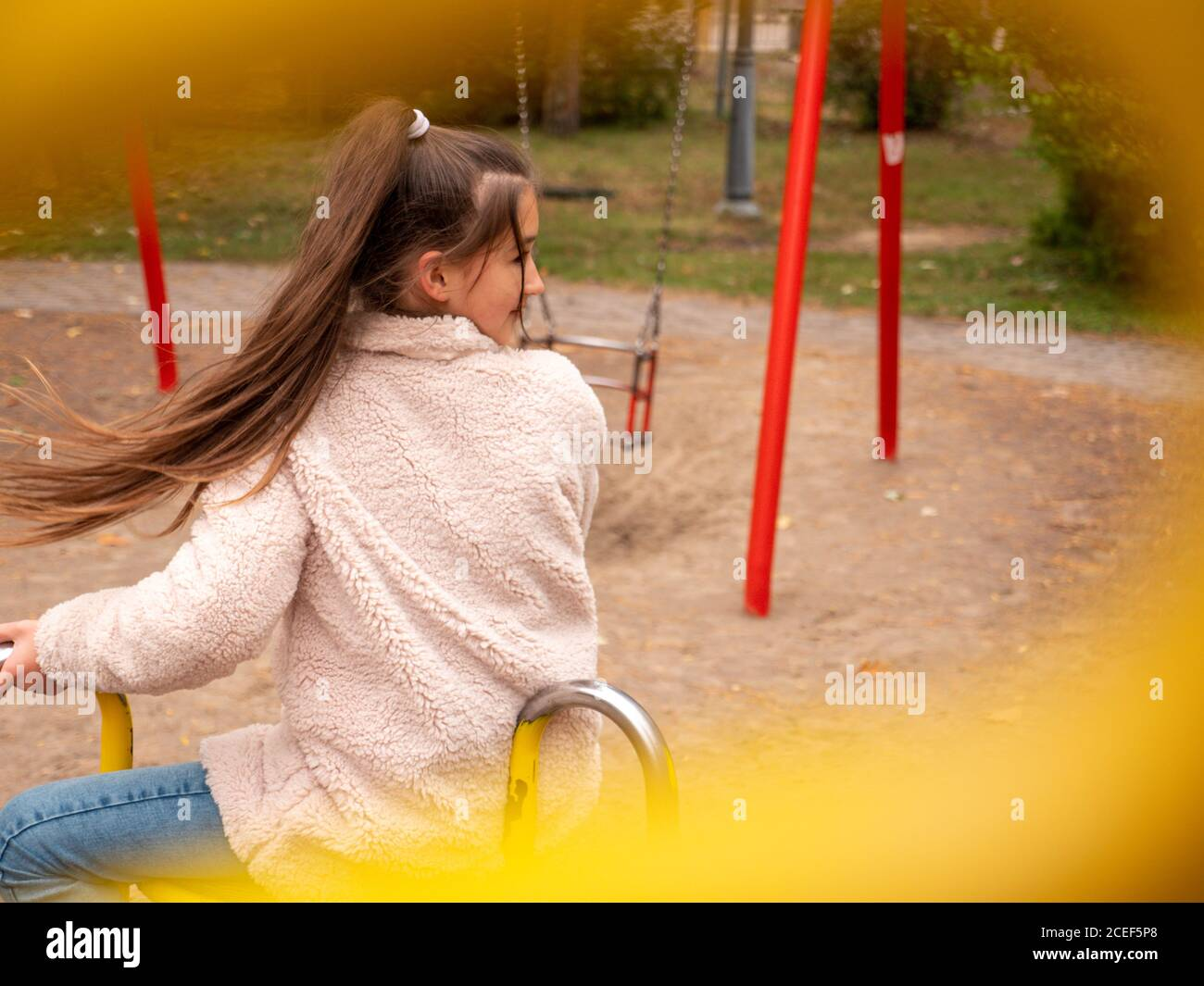 View through railings over happy smiling teenage girl in a faux fur coat and with long ponytail spinning at a merry-go-round at children playground. Stock Photo