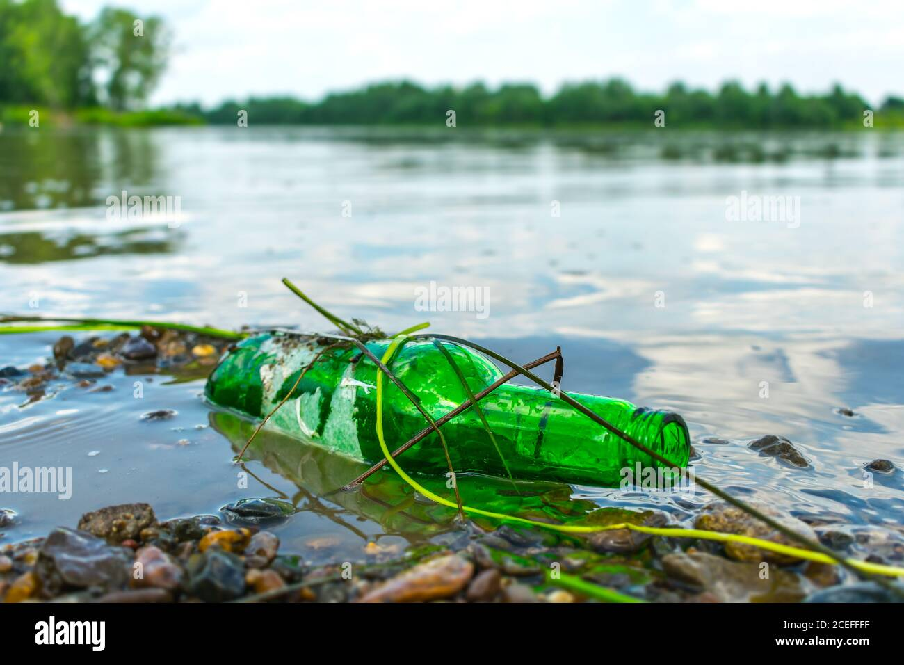 Glass bottle on the riverbank pollutes the environment. Nature pollution with garbage left by vacationers on the beach Stock Photo