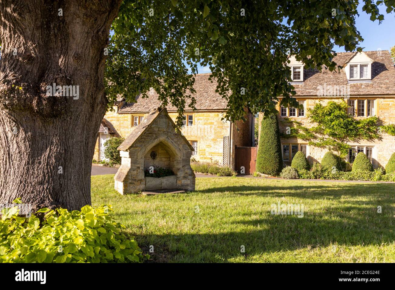 Evening light on cottages beside the village green in the Cotswold village of Lower Slaughter, Gloucestershire UK Stock Photo