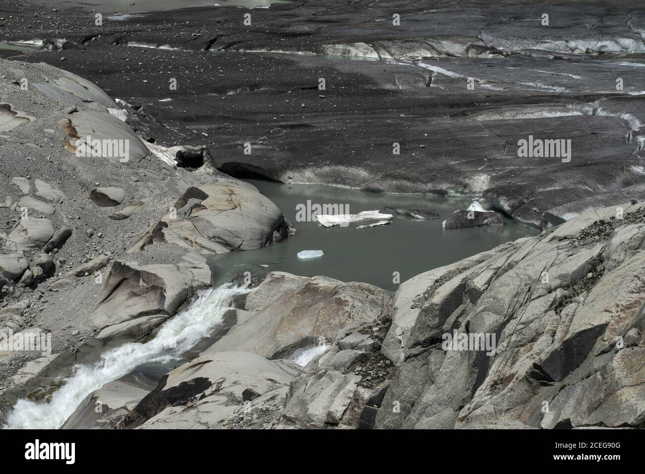 Climate scientists hold global warming responsible for the retreating Rhône Glacier, source of the River Rhône, now melting in summer below the Furka Pass in Valais canton, Switzerland, at a height of about 2,208 m (7,244 ft).  In 1850, a tongue of ice extended well down the side of the mountain before melting in the valley below.  The glacier flows for 7.65 km (4.75 mi) from high Urner Alps snow fields at about 30 to 40 m (100 to 130 ft) per year.  The torrent flowing from the melt water lake begins the river's 813 km (505 mi) journey through southern France to the Mediterranean. Stock Photo