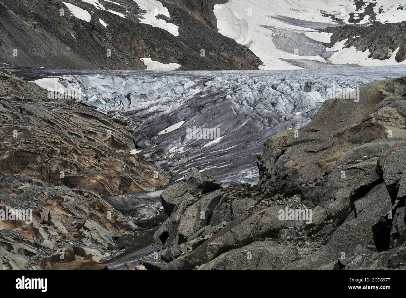 The deeply fissured Rhône Glacier flows at about 30 to 40 m (100 to 130 ft) per year from snow fields on the slopes of the 3,383 m (11,099 ft) Tieralplistock to a point below the Furka Pass in Valais canton, Switzerland, where the ice melts in a green lake at an altitude of about 2,208 m (7,244 ft).  The melt water thunders into the valley basin far below to begin the River Rhône's 813 km (505 mi) journey to the Mediterranean Sea via southern France and the Camargue delta. Stock Photo