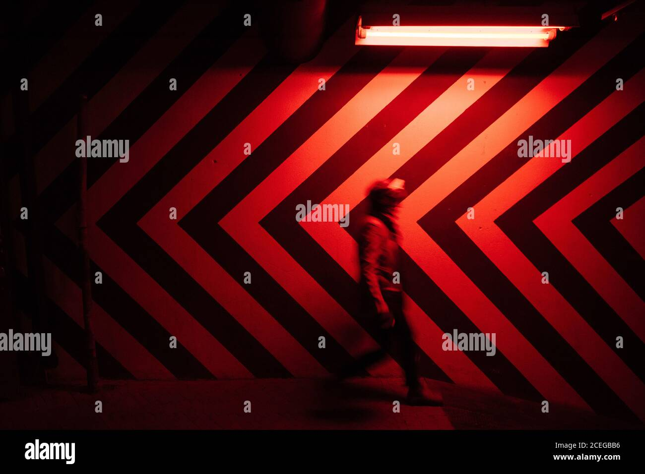 Side view of motion blurred figure of male walking down in tunnel in direction opposite to large red and black arrows on wall lit by red lamps Stock Photo