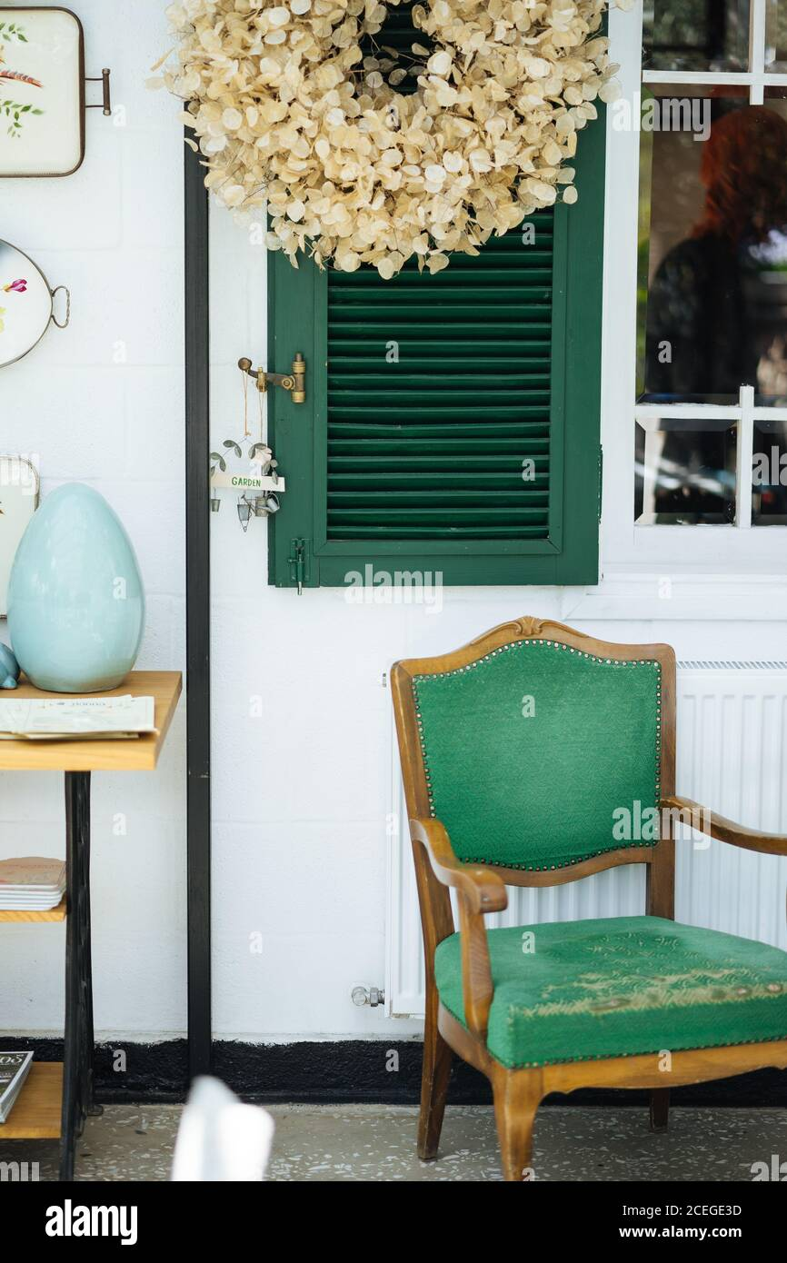 Elegant rural front porch with green window shutters with creative garden sign on it and wooden table with old upholstery chair and dried plant petal wreath hanging above Stock Photo
