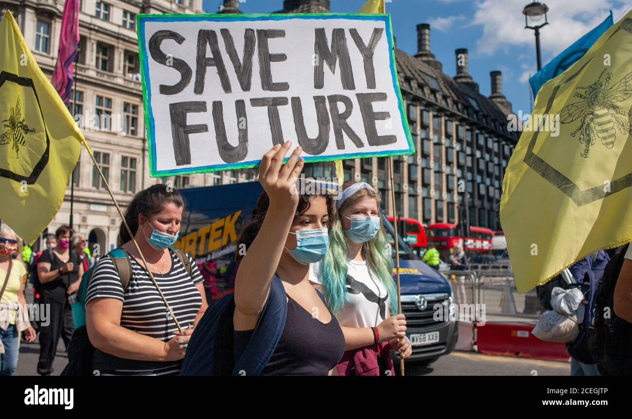 Extinction Rebellion protesters March to the Houses of Parliament, one carrying a sign that reads, 'Save my future', during the 2020 demonstrations. Stock Photo