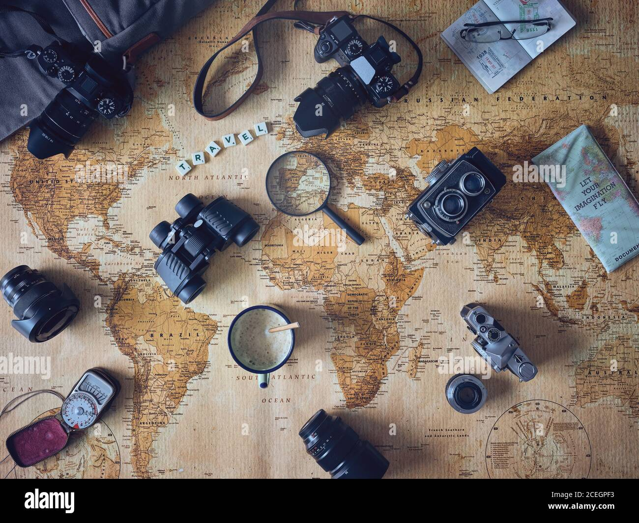 Mug of fresh coffee and assorted tourist stuff lying on retro world map Stock Photo
