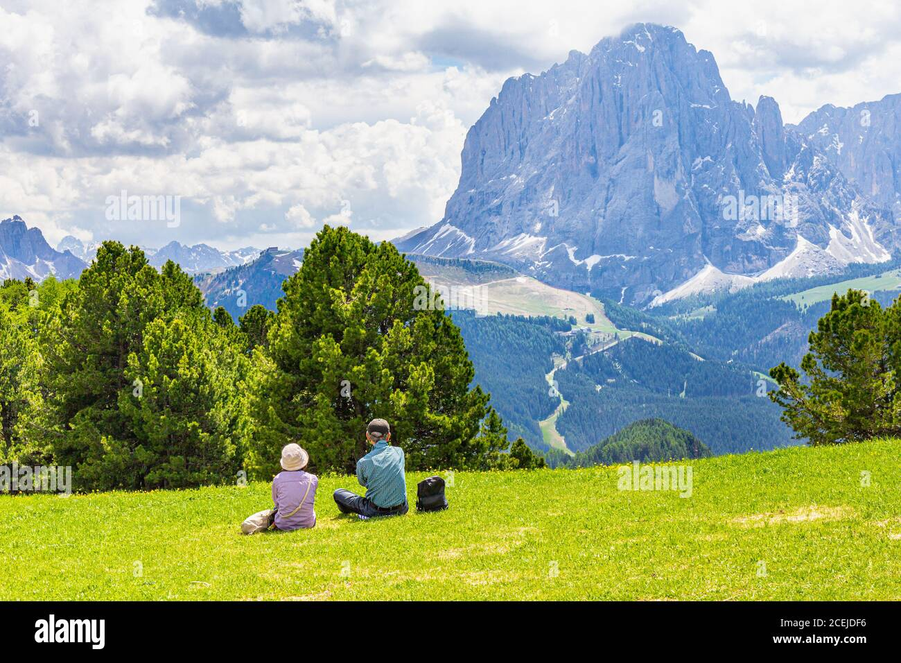 Two elderly people seen at Seceda peak in the background view of the mountain Sassolungo or Longkofel Traveling to village St. Cristina di Val Gardena Stock Photo