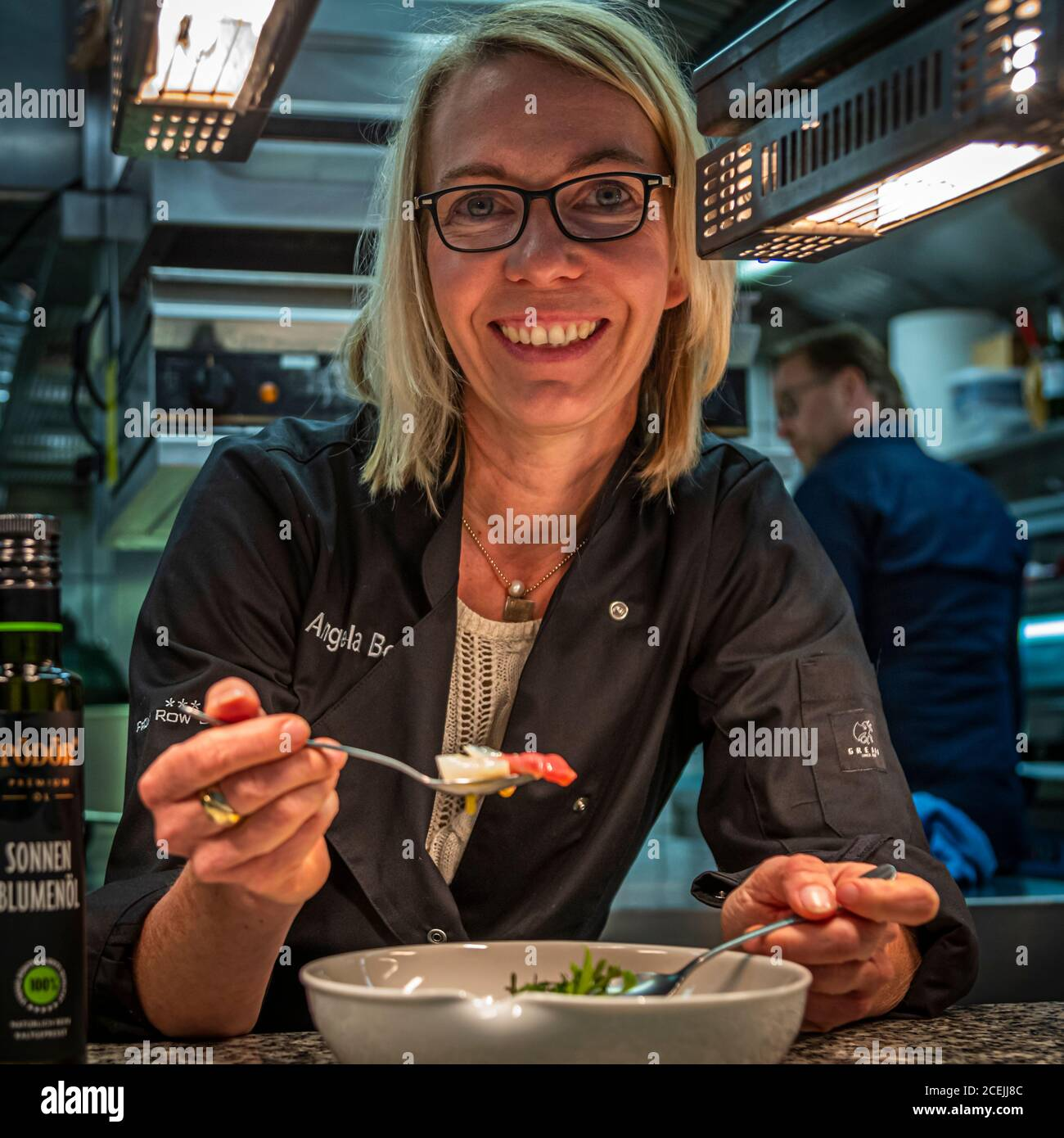 Food Journalist Angela Berg in the kitchen of Michelin Star Chef Thomas Bühner. He works with the cold-pressed vegetable oils from Pödör in Osnabrück, Germany Stock Photo