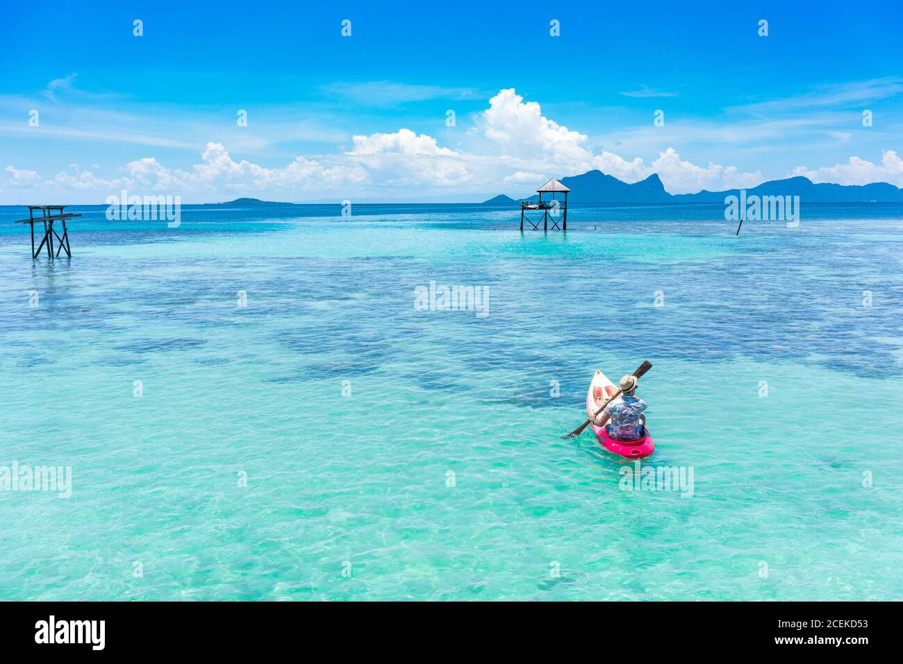 Back view male boating on canoe with paddle on amazing azure sea and blue sky in Malaysia Stock Photo