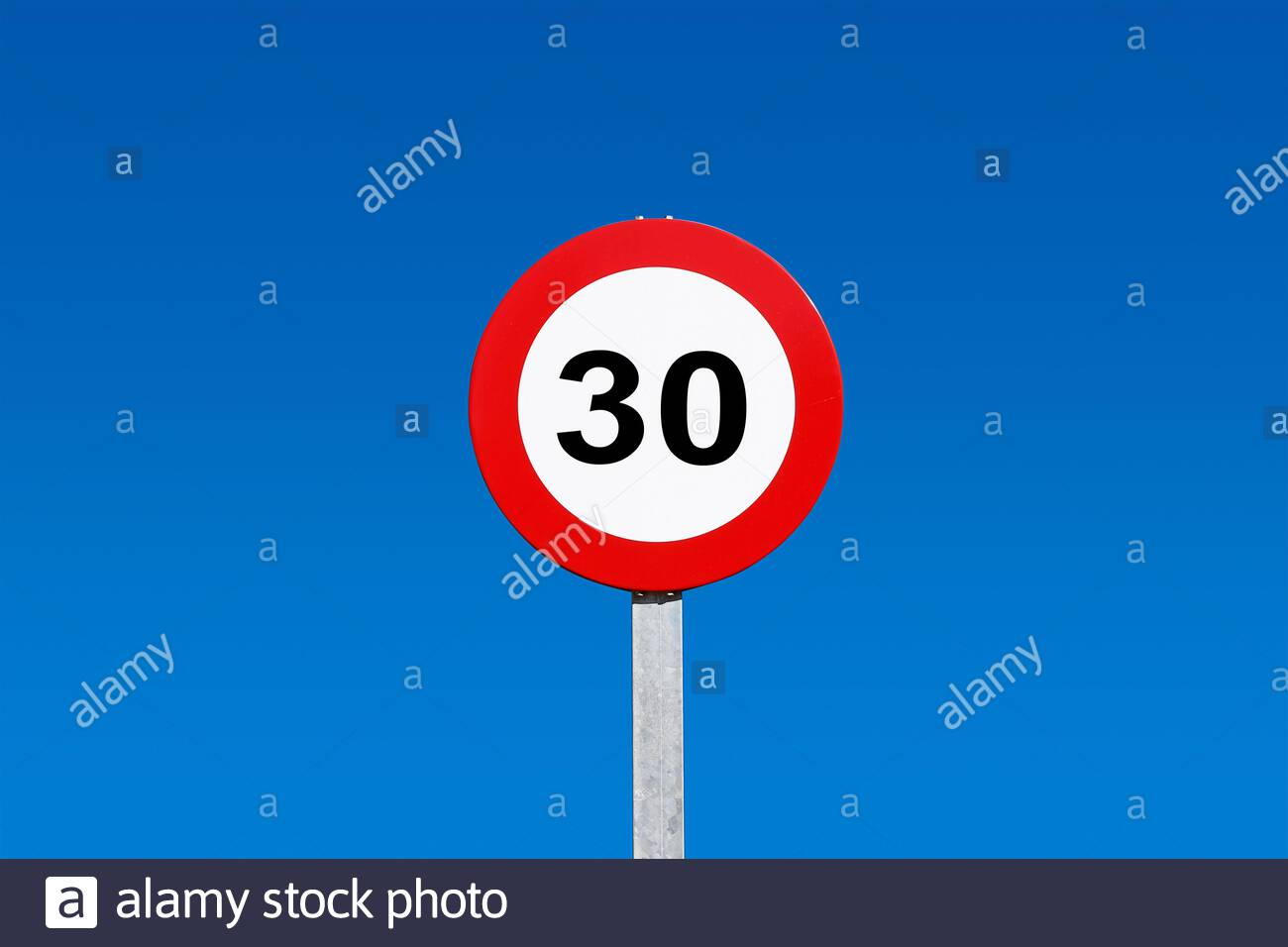 Traffic signs against blue sky 30km / h speed limit sign with a blue sky in the background Stock Photo