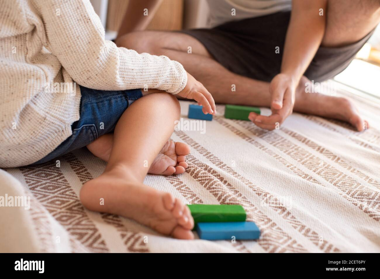 Little kid and his father playing at home with wood building blocks. Homeschooling. Stay at home. Family time Stock Photo
