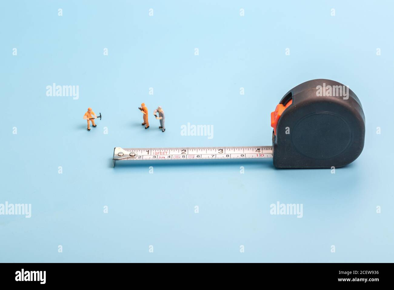 Meter stick and worker on blue background Stock Photo