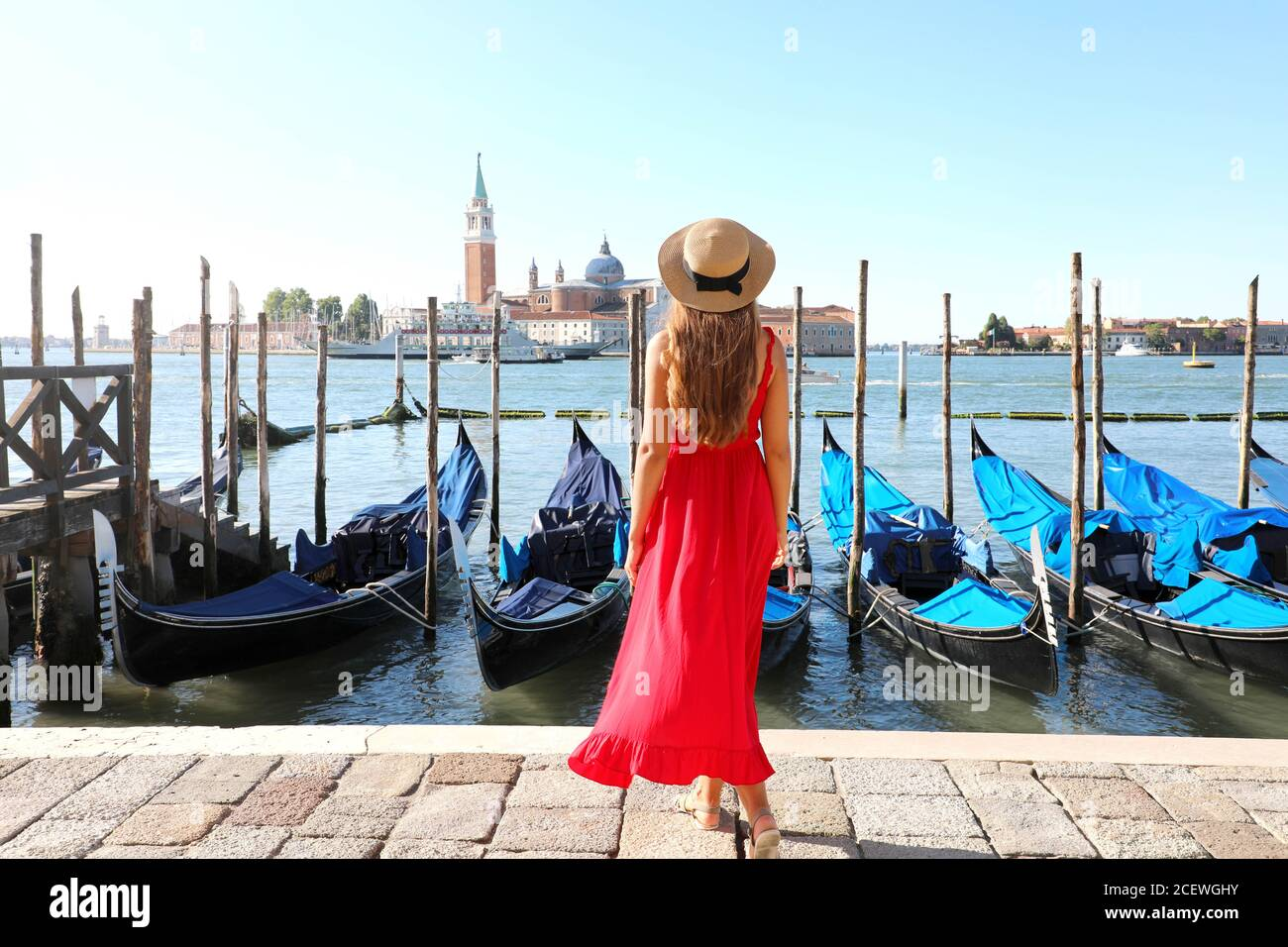 Holidays in Venice. Back view of beautiful girl in red dress enjoying view of Venice Lagoon with the island of San Giorgio Maggiore and gondolas moore Stock Photo