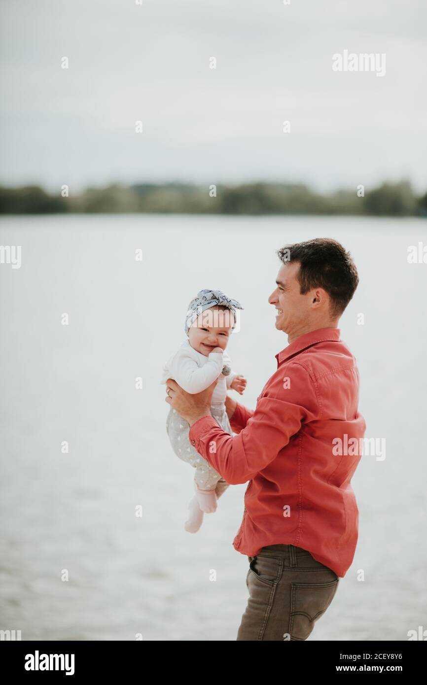 family, parenthood, fatherhood and people concept - happy man and little girl in having fun in summer park Stock Photo