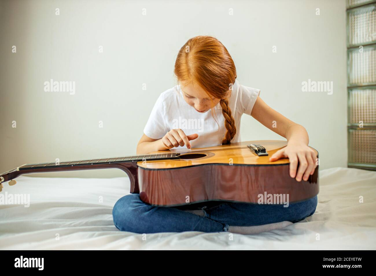 cute adorable child blogger play guitar, talk at camera how she learned playing acoustic guitar, she is self-taught Stock Photo