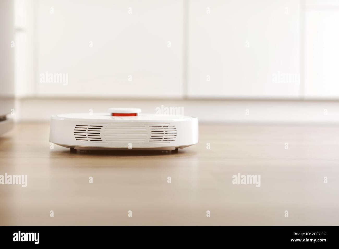 White robotic vacuum cleaner on laminate floor cleaning dust in living room interior. Smart electronic housekeeping technology. smart home Stock Photo