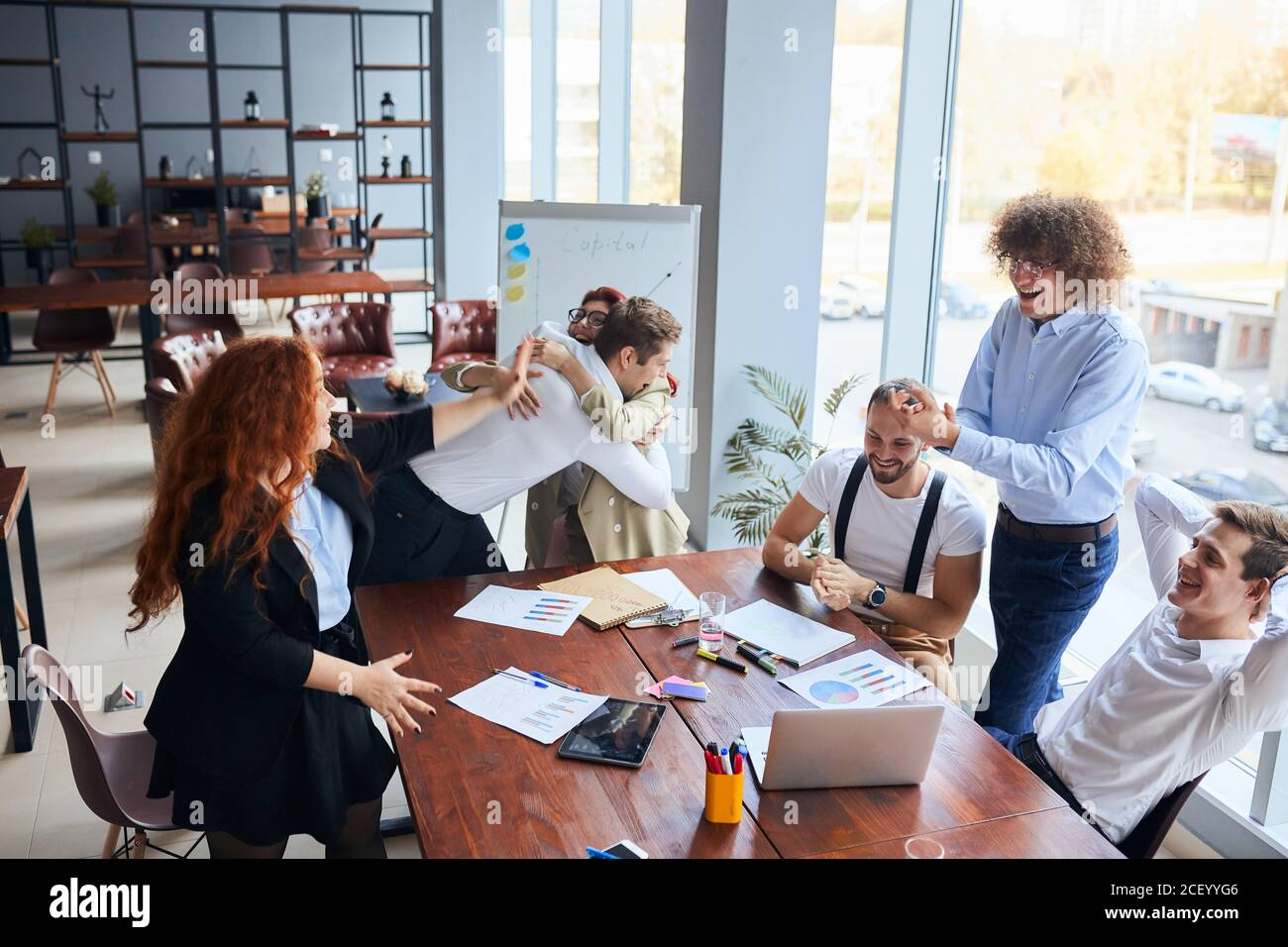 Everyday winners. Cheerful group of happy business people in formal wear looking at the laptop and gesturing, celebrate winning Stock Photo