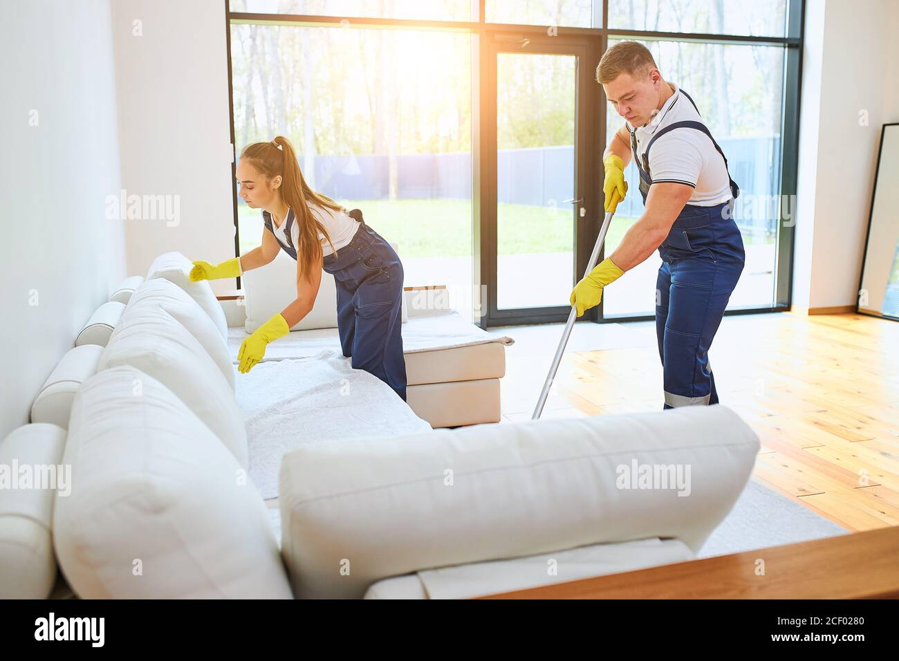 Two janitors in uniform cleaning new room with white sofa, mopping floor, straighten sofa. Work in country house, cottage Stock Photo