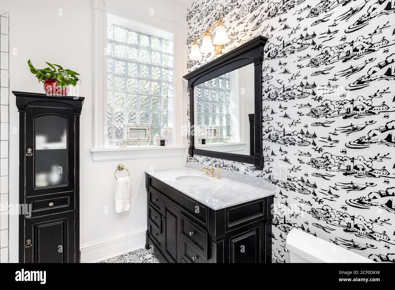 A Renovated Black And White Bathroom With Wallpaper Black Vanity Decorative Tiles On The Floor And Subway Tiles In The Shower Stock Photo Alamy