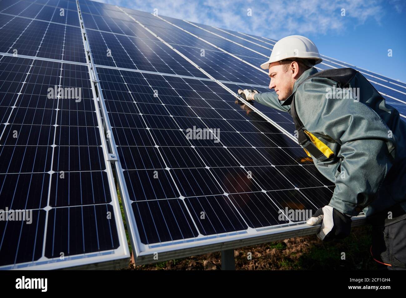 Professional worker, wearing protective suit, helmet and gloves, installing a photovoltaic solar batteries on a sunny day. Concept of alternative energy and power sustainable resources. Stock Photo