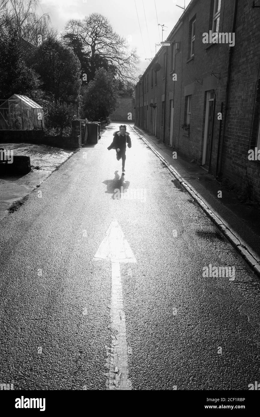 Boy running on sunny road Stock Photo