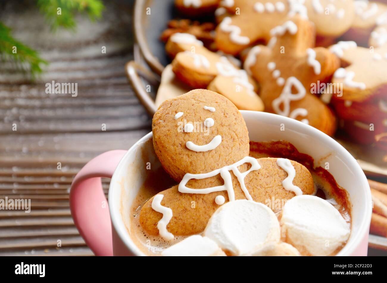 Pink mug with hot chocolate marshmallows and gingerbread man closeup. Stock Photo