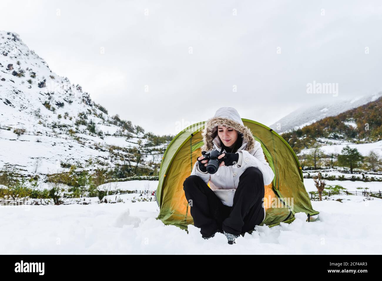 Content female in white winter jacket and black pants sitting with camera near light green tourist tent on snow in mountains Stock Photo