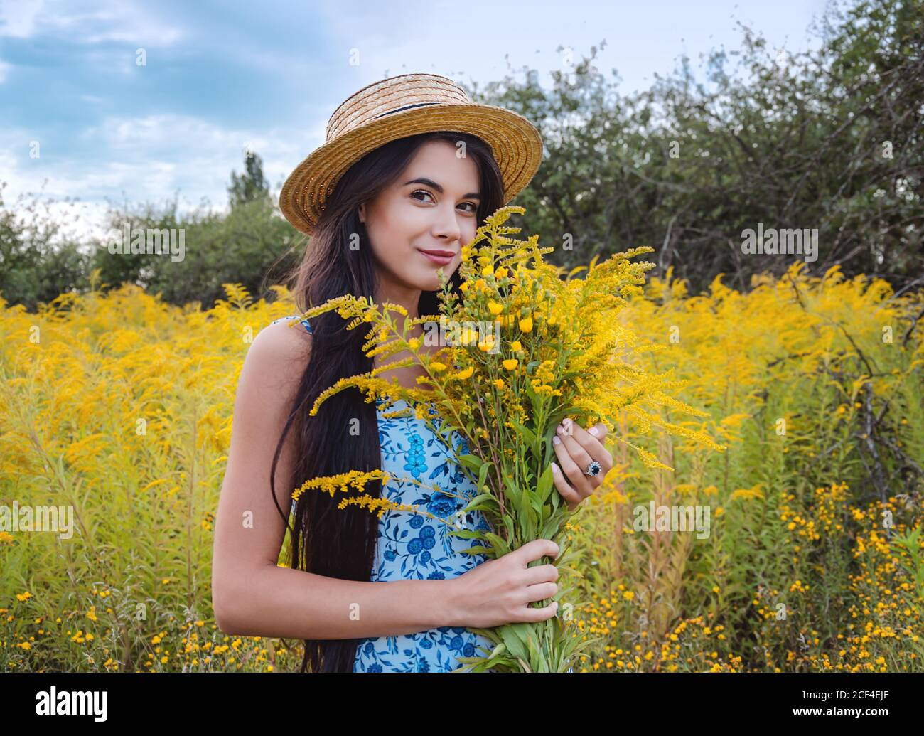 young girl in a straw hat surrounded by blooming yellow herbs, close up Stock Photo