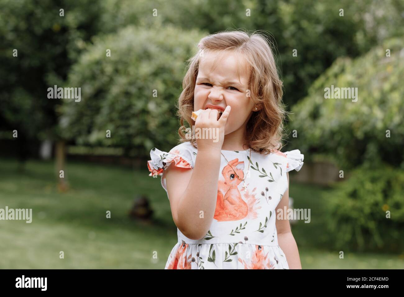 Funny kid girl eating sandwich outdoors. Having fun. Looking at camera. Posing over nature background. Healthy food. Childhood. Stock Photo