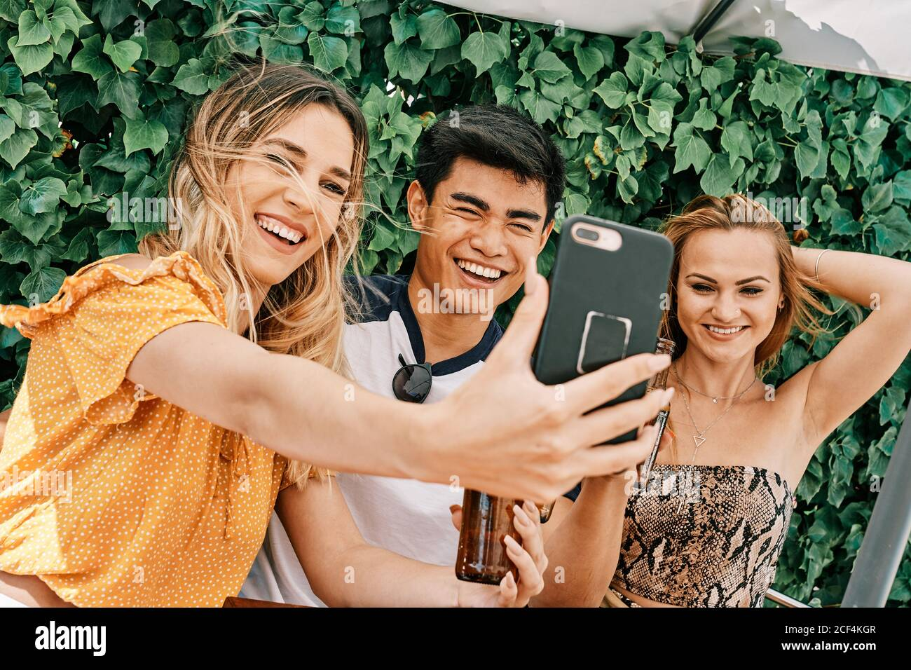 two women and a man drinking beer and taking selfies Stock Photo