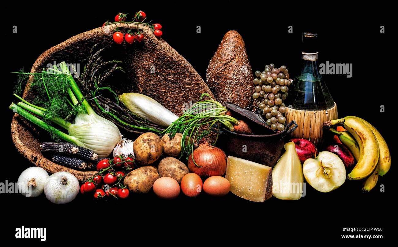 A beautiful still life on a black background with tomatoes, grapes, potatoes, onions, garlic, fennel, eggs, carrots, bread, bananas, cheese, red apple Stock Photo
