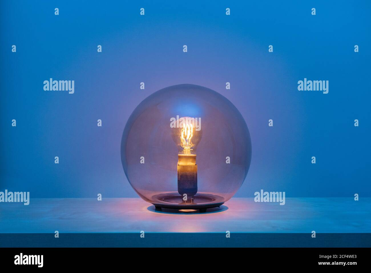 Modern turned on luminaire with light bulb inside thin transparent glass sphere in middle of shelf in blue room at dusk Stock Photo