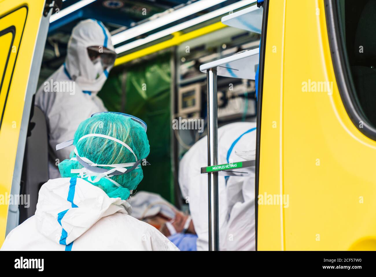 Side view of anonymous doctors in protective suit standing in ambulance car near opened door with equipment and examining patient with virus infection Stock Photo