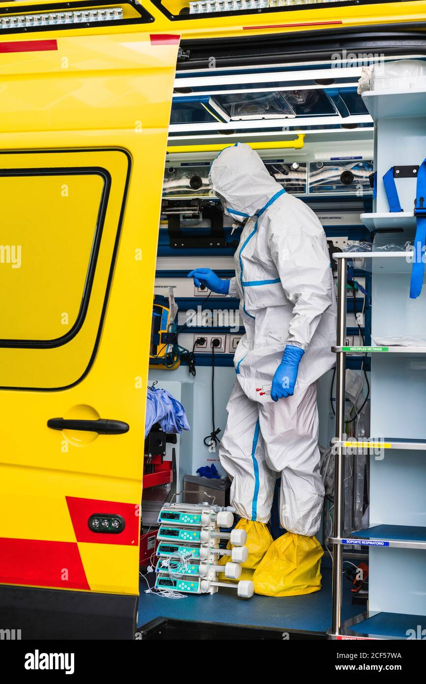 Side view of anonymous doctor in protective suit standing in ambulance car near opened door with equipment and examining patient with virus infection Stock Photo