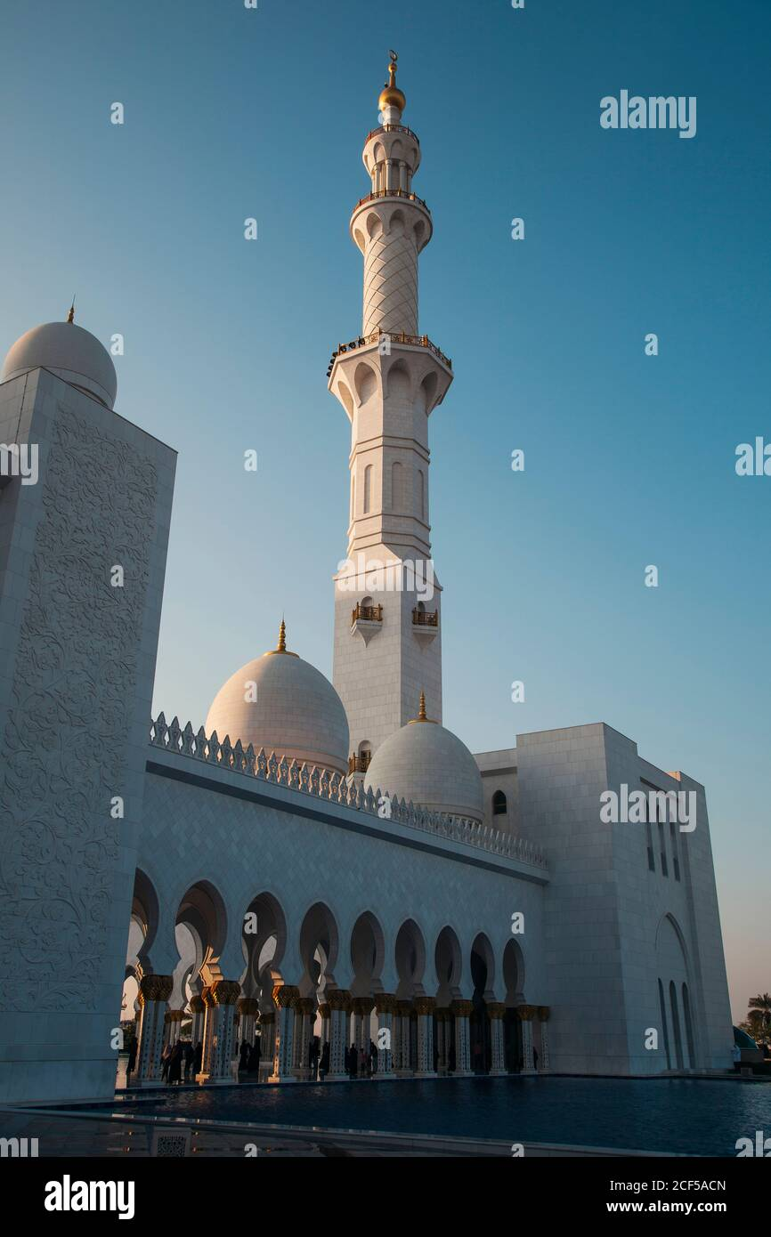 Amazing huge mosque with high tower near pool and blue sky in Abu Dhabi, United Arab Emirates Stock Photo