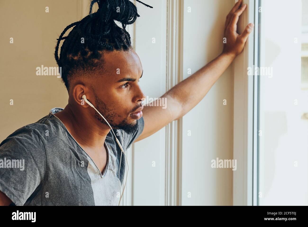 Side view of serious ethnic man with creative hairstyle listening to music and leaning on window frame Stock Photo