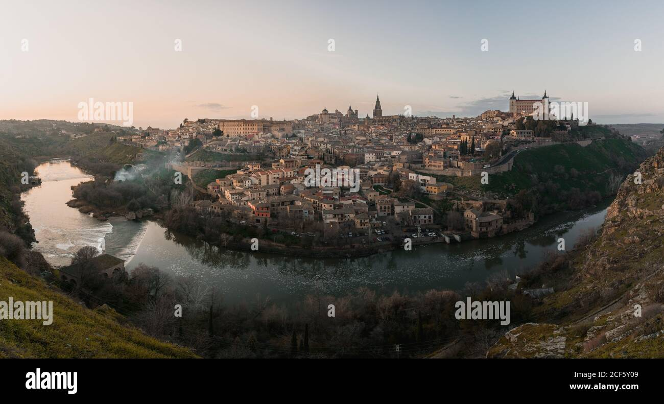 Panoramic view across river of old city Toledo in Spain with medieval castles and fortresses at sunset time with cloudy sky and reflection in river water Stock Photo