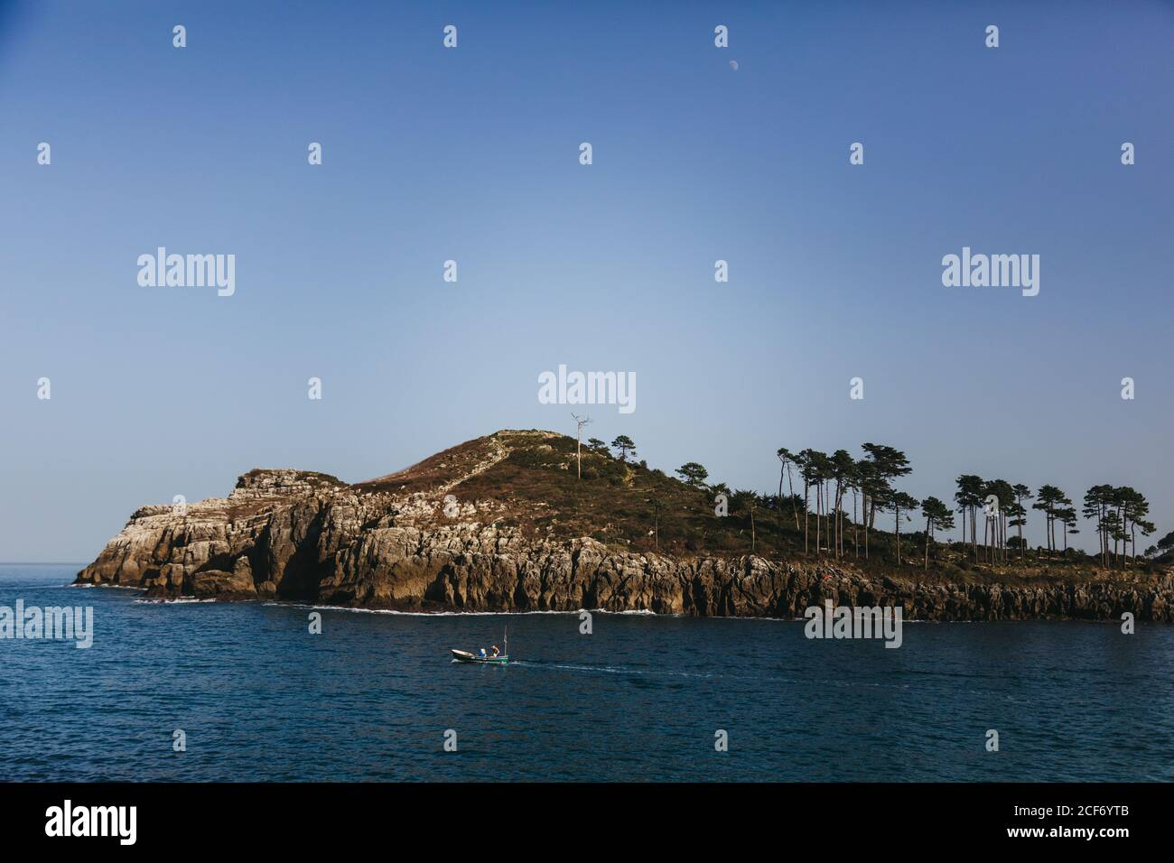 Lonely fishing boat moving on bay with tranquil water against rocky shore with tall evergreen trees at foot of hill under clear blue sky in Spain Stock Photo