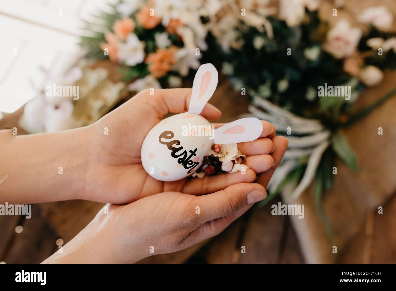 young woman holding an easter egg with rabbit ears painted by children with flowers Stock Photo