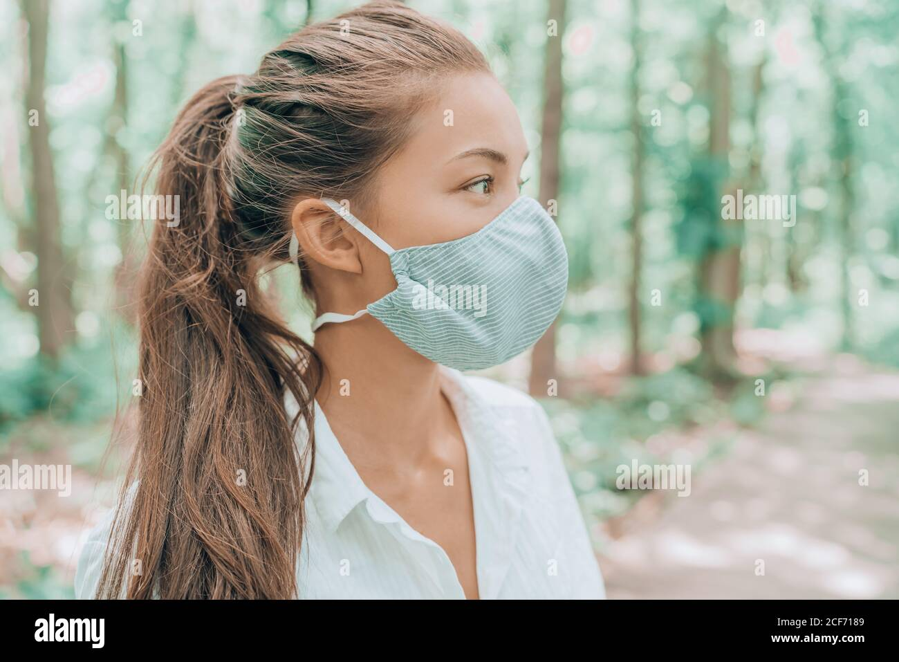 Face mask of cotton fabric are breathable for skin. Asian woman wearing corona virus mouth covering walking outdoors in woods Stock Photo
