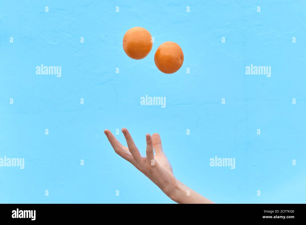 Crop woman tossing fresh orange in air showing concept of healthy diet on blue background Stock Photo