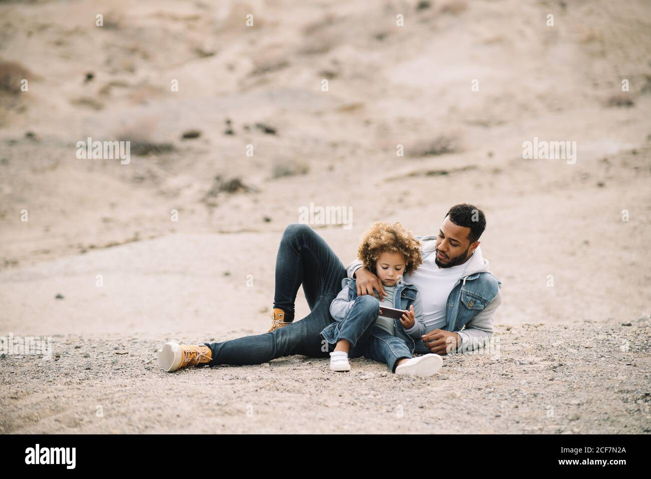 African American bearded casual man lying on sandy ground leaning on elbow and bending leg at knee looking at curly ethnic toddler in denim clothes sitting beside with mobile phone Stock Photo