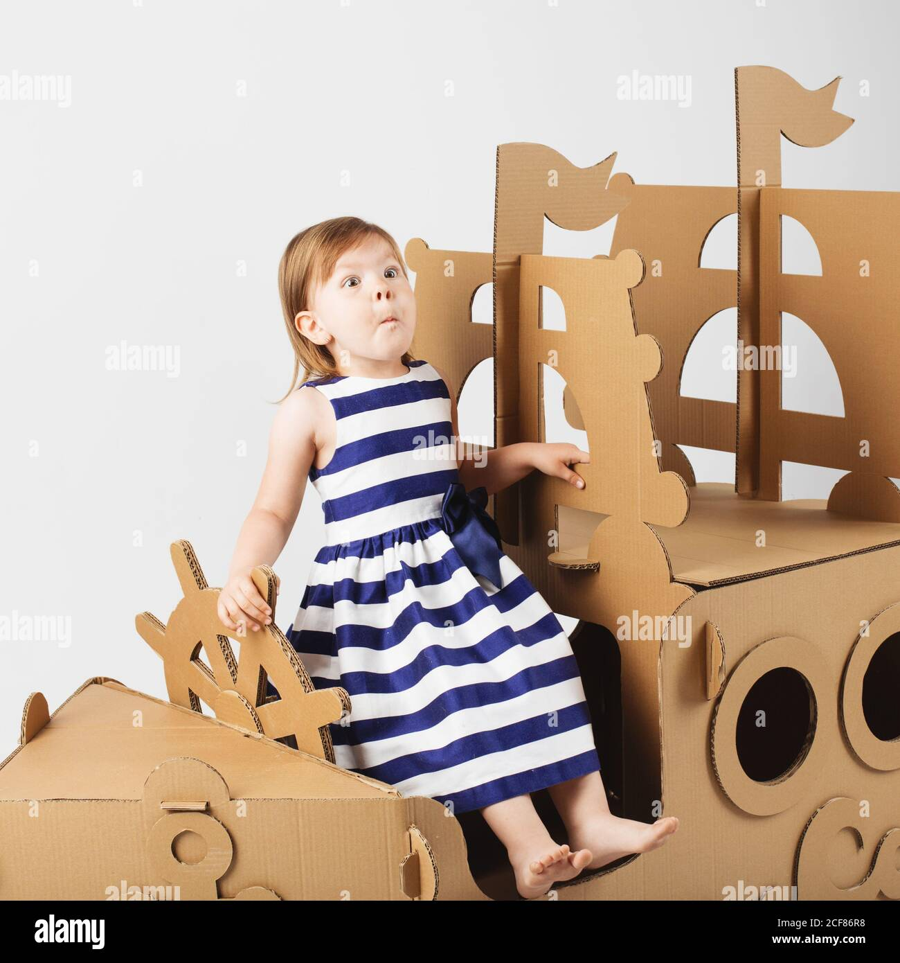 Cute  Little girl wearing striped dress in a marine style playing with cardboard ship on white background. Happy children. Childhood. Fantasy, imagina Stock Photo