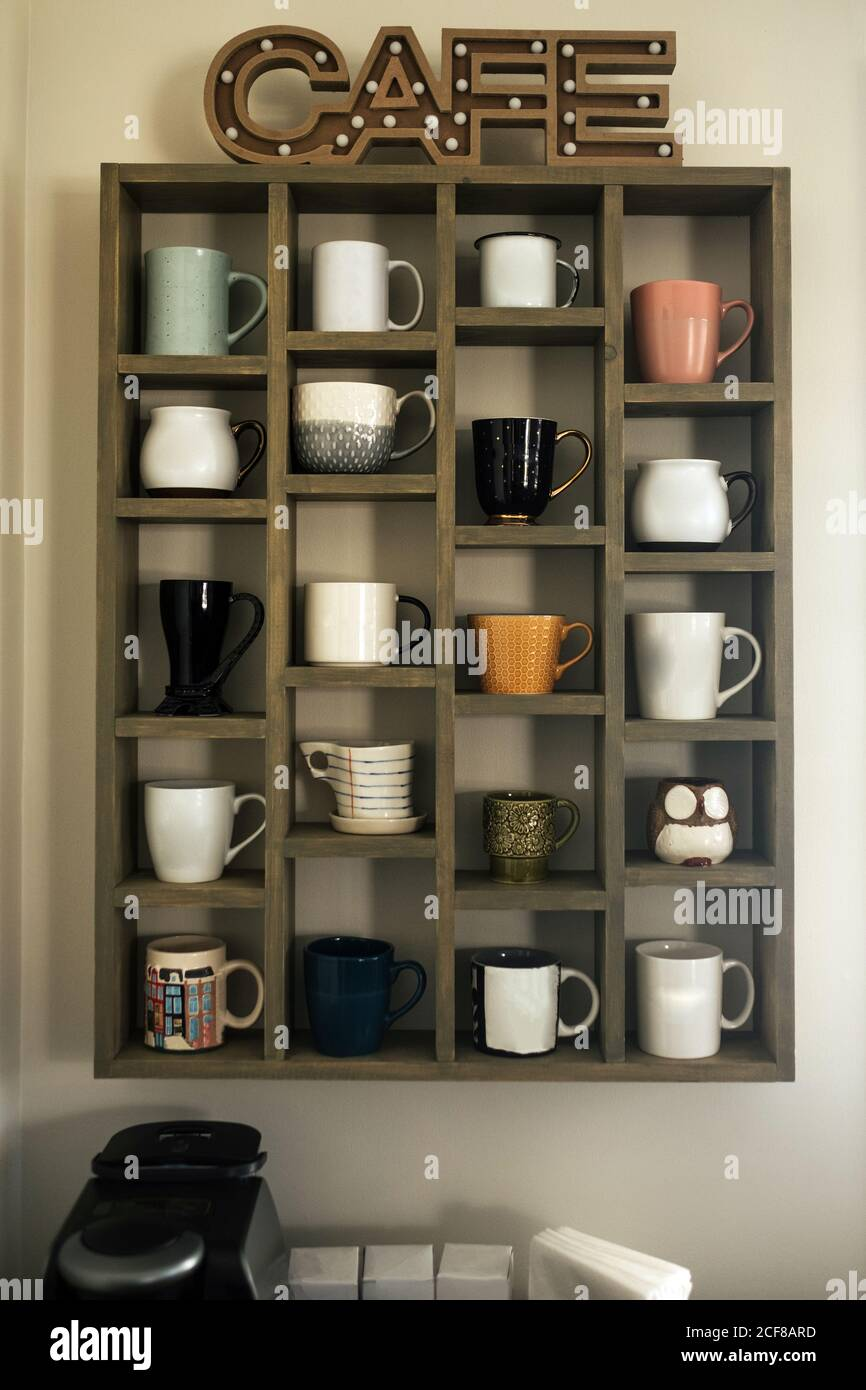 Wooden Sideboard With Collection Of Ceramic Coffee Mugs And Tea Cups Separated With Partition And Big Letters With Word Cafe Above In Kitchen Stock Photo Alamy
