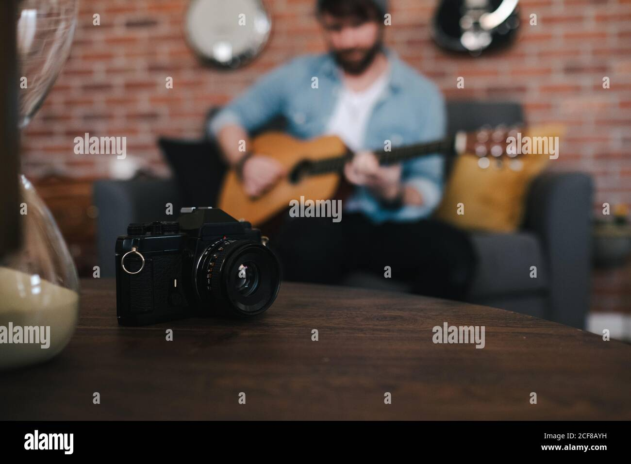 Crop bearded guy in denim jacket playing acoustic guitar while sitting on cozy couch in front of wooden table with photo camera and hourglass at home Stock Photo