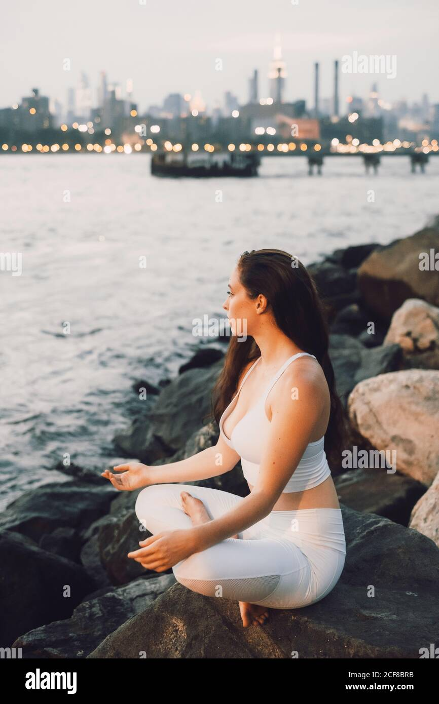 From above side view of concentrated female in activewear sitting on stone at waterfront while practicing yoga on background of evening cityscape and looking away Stock Photo
