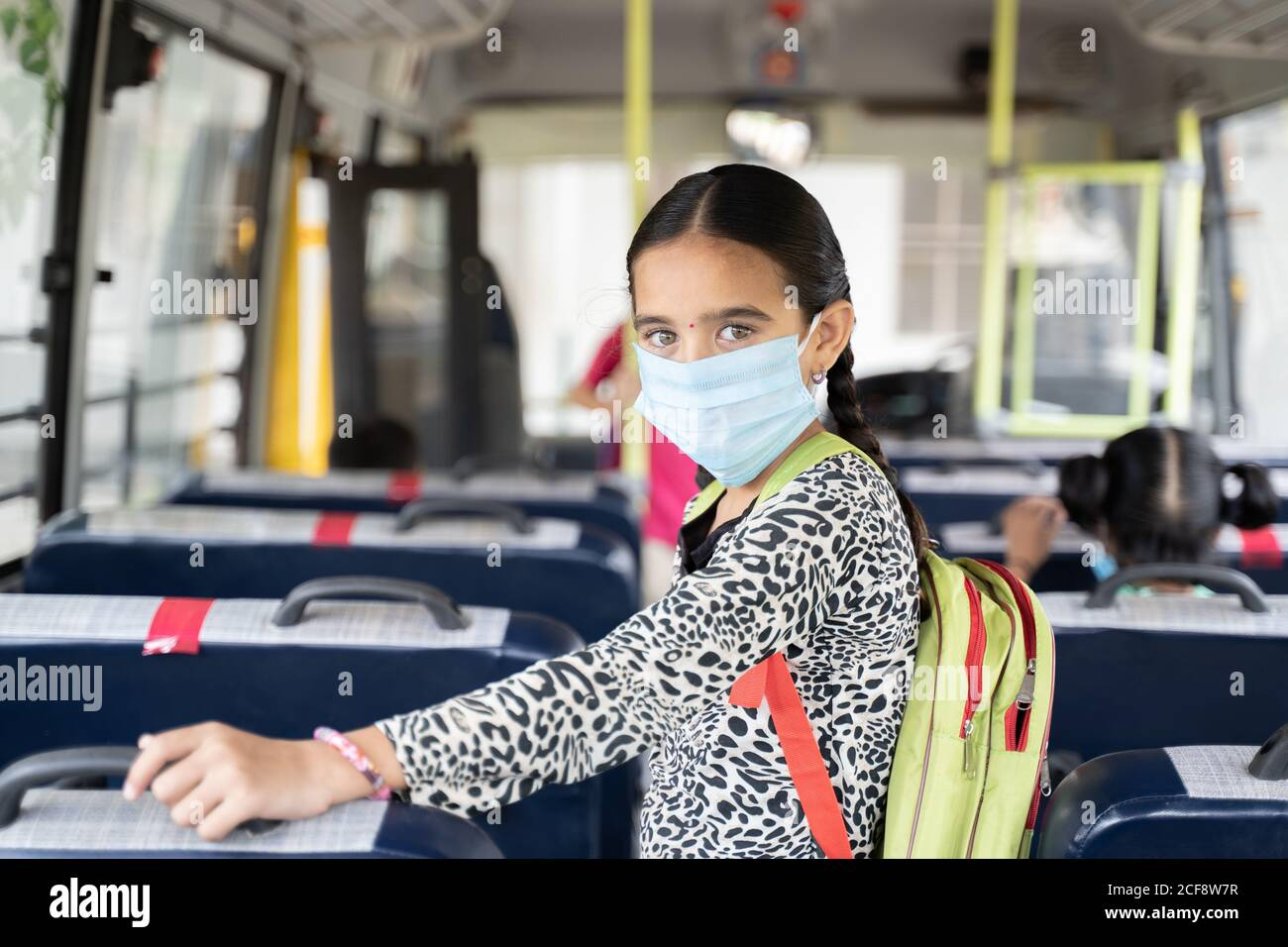 Portrait of Girl kid student in medical mask inside the school bus looking at camera - Concept of school reopen or back to school with new normal Stock Photo