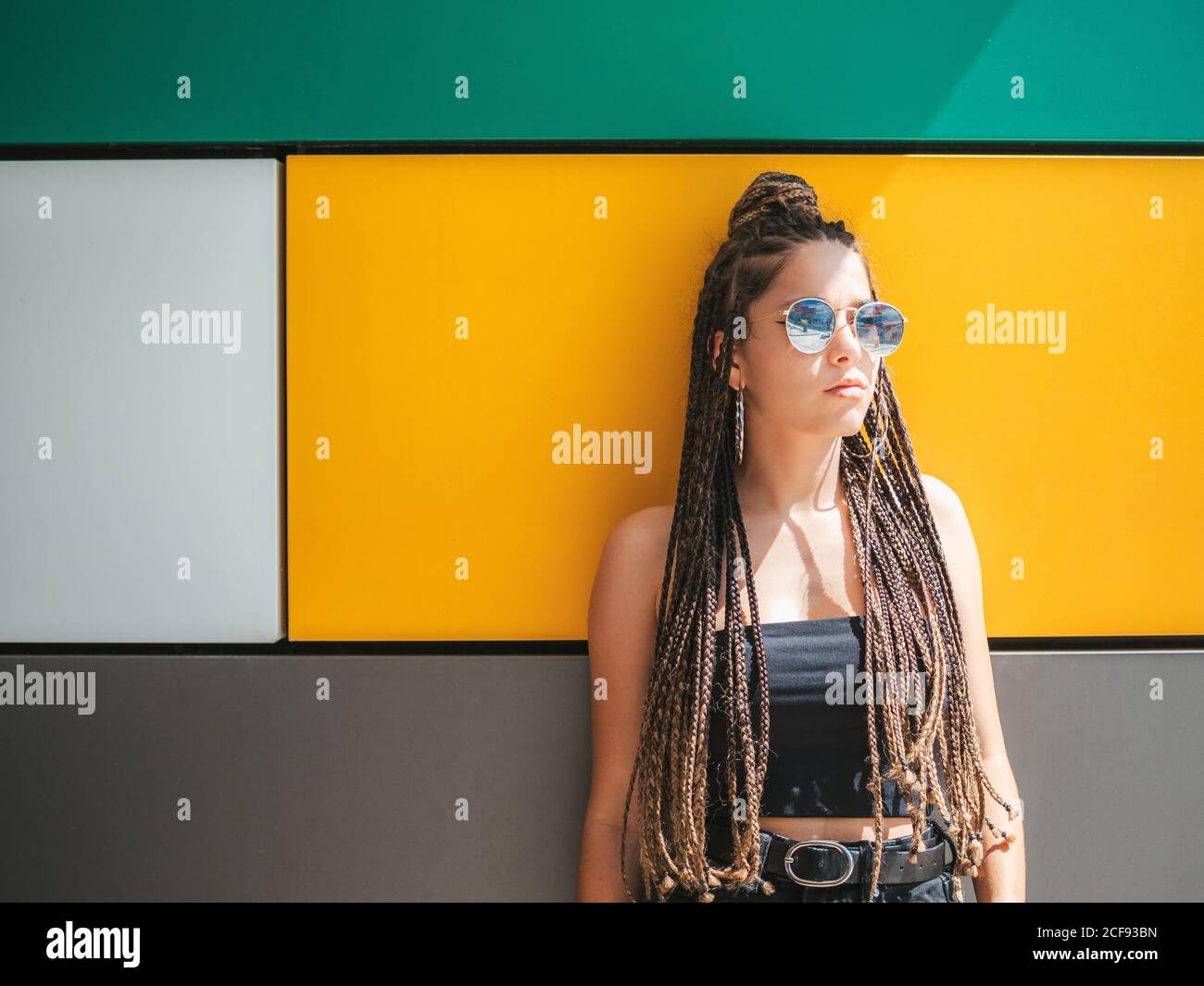 Pretty stylish teenage girl with hands in pocket and unique dreadlocks looking away on colorful background Stock Photo